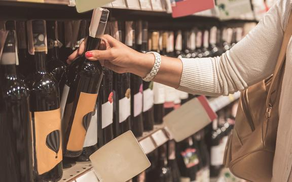 Woman is standing near shelf with bottle of wine and choosing one. Close up of female hand, rising beverage