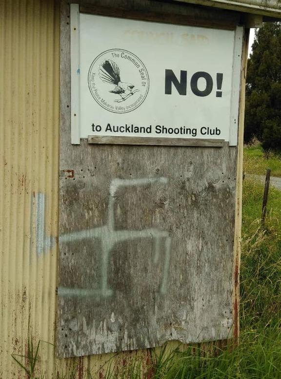 A swastika sprayed on to a shed with protest signs on the neighbouring property to the gun club.