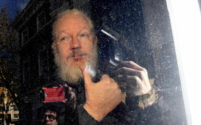 Julian Assange gestures as he arrives at Westminster Magistrates' Court in London, after the WikiLeaks founder was arrested by officers from the Metropolitan Police and taken into custody Thursday April 11, 2019.
