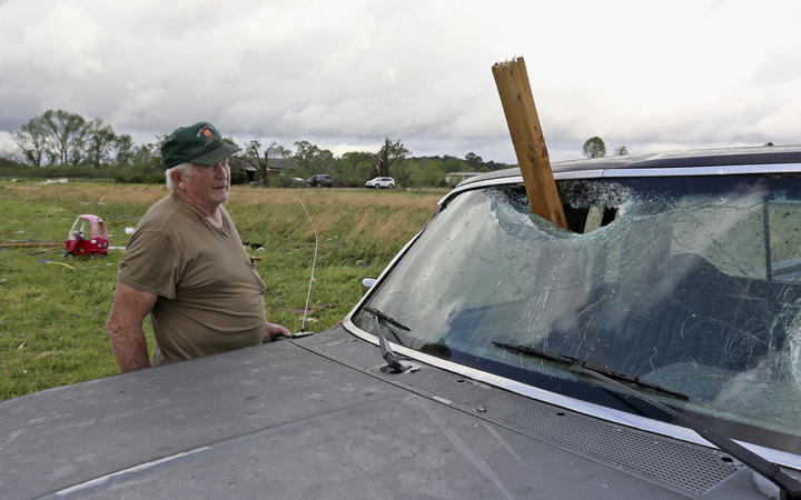 A man looks at a piece of wood that was blown through the windshield of his daughter's truck in Hamilton, Miss., after a storm moved through the area Sunday, April 14, 2019.