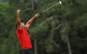 Tiger Woods celebrates after sinking his putt on the 18th green to win during the final round of the Masters at Augusta National Golf Club on April 14, 2019 in Augusta, Georgia.