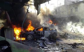 Smoke rises as the car burning after a car bomb blast in October 2013, in Darkush, Idlib, Syria. At least 20 people killed when the car exploded in a bazaar.