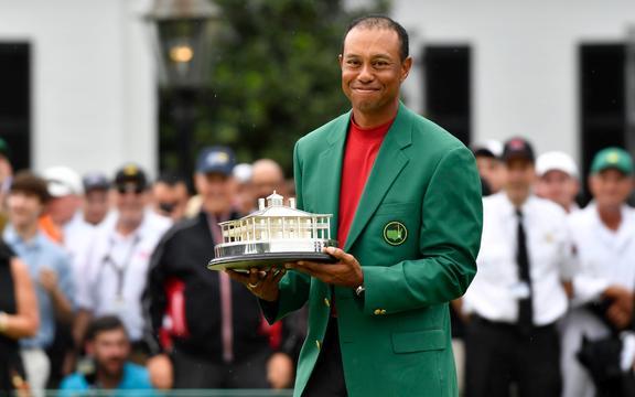在奥古斯塔国家高尔夫俱乐部赢得大师赛高尔夫锦标赛后,老虎伍兹以绿色夹克和奖杯庆祝。