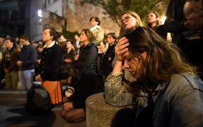 People kneel to pray on the pavement as flames engulf Notre-Dame Cathedral in Paris on April 15, 2019. - A