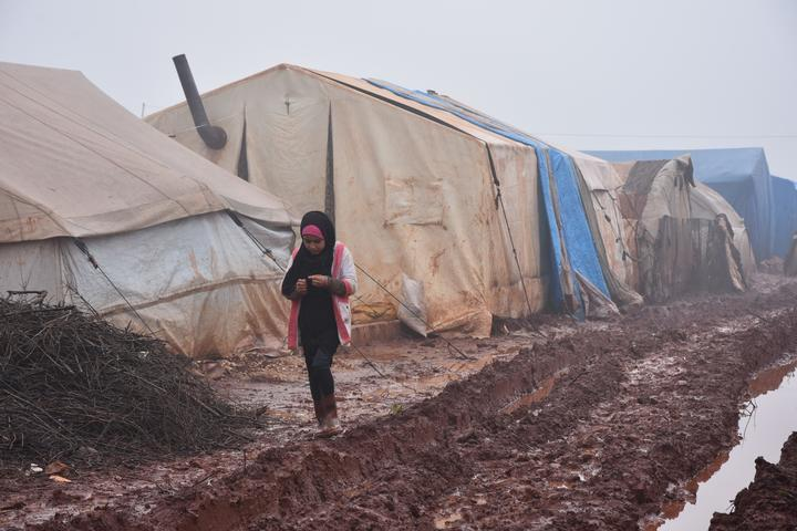 A girl walking in the mud outside her shelter at Al-Ihsan refugee camp as Syrians enduring harsh winter at the camp in Idlib, Syria on January 15, 2019.