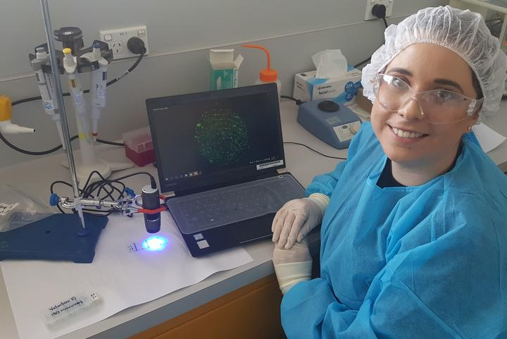 ESR researcher Alicia Haines with a handheld microscope connected to a computer showing an image of fluorescent DNA in a fingerprint.