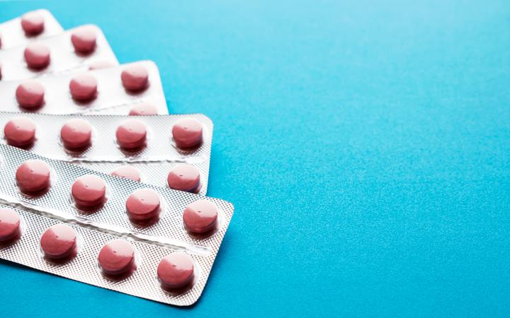 Pink tablets in blisters on a blue background. Many packages of pills in silvery blisters. Statins, enzymes, analgesics, antibiotic. Copy space. Healthy, Pharmacy and medical concept