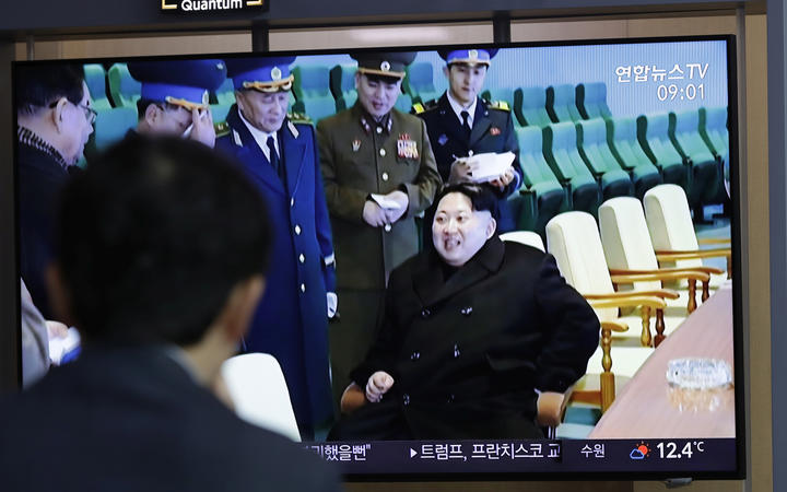 A man watches a TV news program reporting about North Korea's test-fire of a