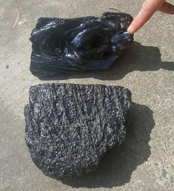 A piece of lava poured in the Lava Lab and a piece of real lava cut out of a Hawaiian lava flow.