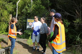 Auckland Council officers talk to trampers in the Waitākere Ranges.