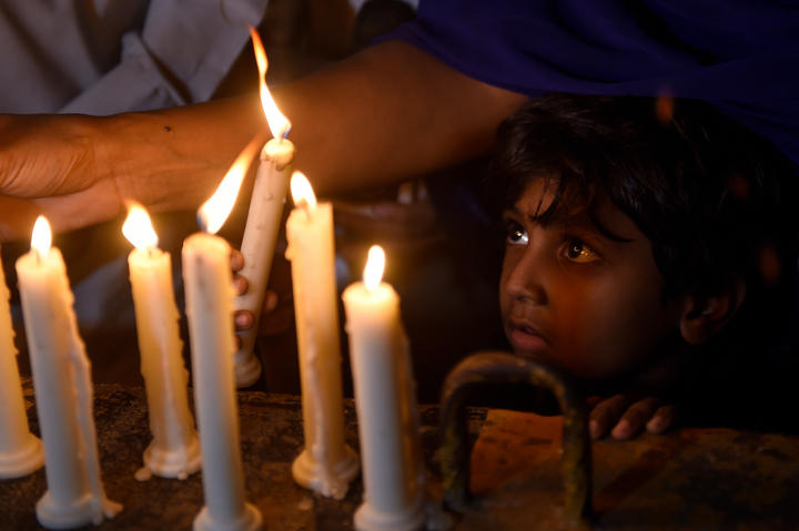 A Pakistani Christian child looks on as adults light candles to pay tribute to Sri Lankan blasts victims in Karachi on April 21, 2019.