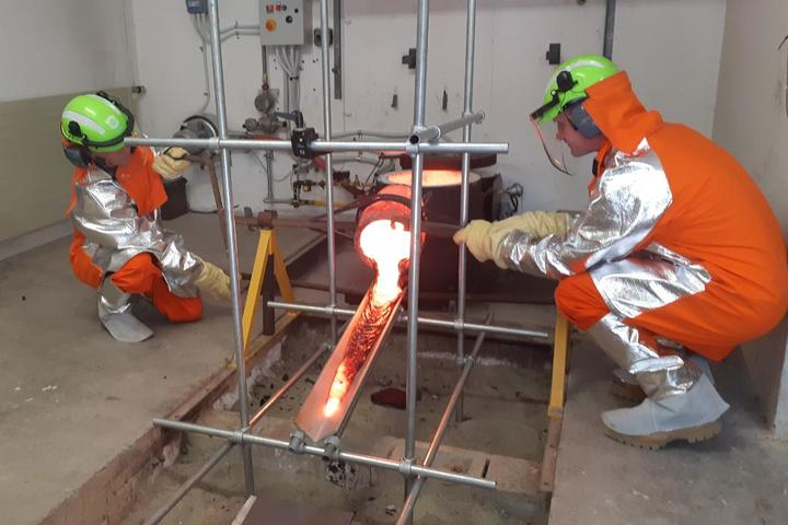 Scientists wearing protective Kevlar clothing pour molten lava from a crucible in the Lava Lab.