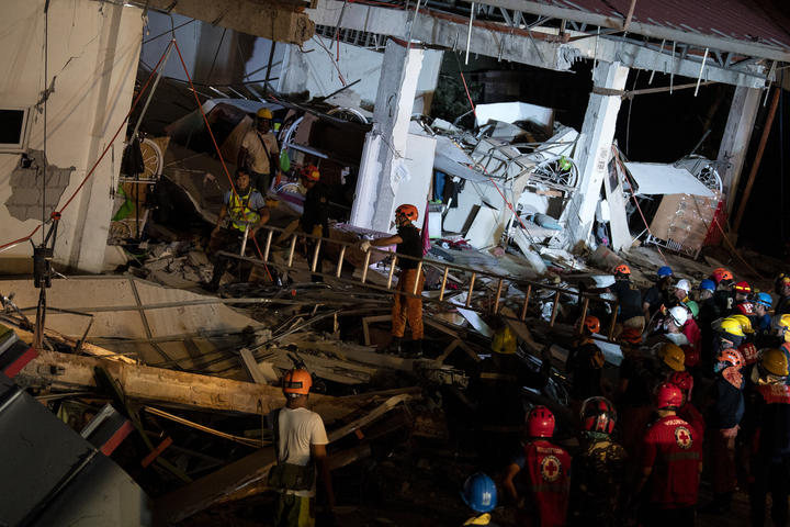 Rescue workers search for survivors in a collapsed Chuzon Super Market in Porac, Pampanga, after a powerful earthquake hit northern Philippines on April 22, 2019.