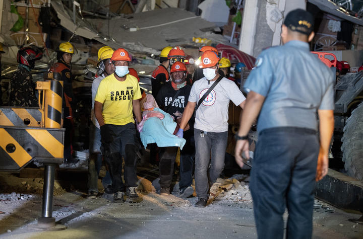 Rescue workers carry victim from a collapsed Chuzon Super Market in Porac, Pampanga, after a powerful earthquake hit northern Philippines on April 22, 2019.