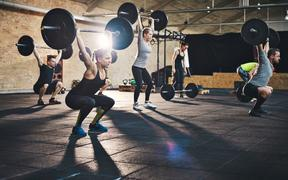 Group of young muscular adult male and females lifting large barbells in cross-fit class with thick mats and brick walls