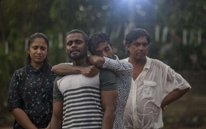Mourners grieve at the burial of three members of the same family victims of Easter Sunday bomb blast at St. Sebastian Church in Negombo, Sri Lanka, Monday, April 22, 2019.