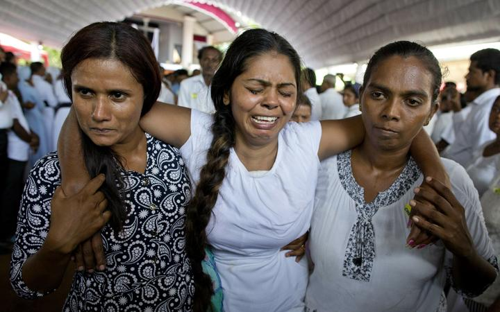 A grieving woman is supported during a funeral service attended by Cardinal Malcolm Ranjith for Easter Sunday bomb blast victims at St. Sebastian Church in Negombo, Sri Lanka, Tuesday, April 23, 2019.