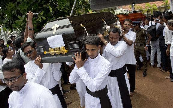 Clergymen carry coffins for burial during a funeral service for Easter Sunday bomb blast victims at St. Sebastian Church in Negombo, Sri Lanka, Tuesday, April 23, 2019.