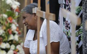 An elderly Sri Lankan woman cries sitting next to the grave of her family member who died in a Easter Sunday church explosion in Katuwapitiya village in Negombo, Sri Lanka