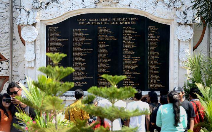 Tourists look at a large marble plaque listing the victims as they visit the Bali bombing memorial on the 13th anniversary of the 2002 blasts.