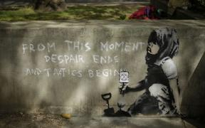 Dappled shade from a tree is cast over a new piece of street art that  is believed to be by street artist Banksy on a wall where Extinction Rebellion climate protesters had set up a camp in Marble Arch, London, Friday, April 26, 2019.