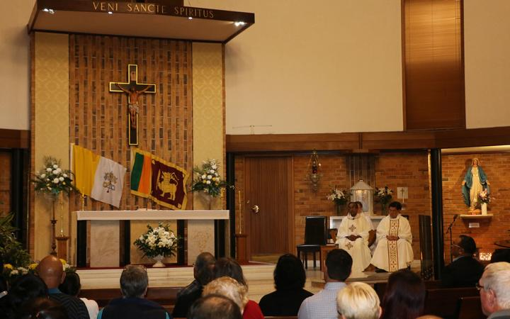 Father Jue Algama (L) from St Mary's Catholic Church in Northcote led the service.