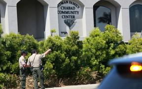 San Diego Sheriff deputies look over the Chabad of Poway Synagogue after a shooting.
