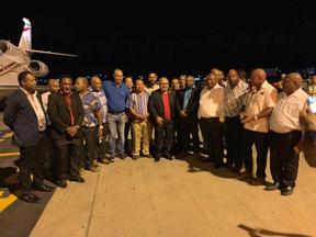 Papua New Guinea prime minister Peter O'Neill (centre, red shirt) surrounded by MPs afer arriving at Port Moresby's Jackson's Airport.