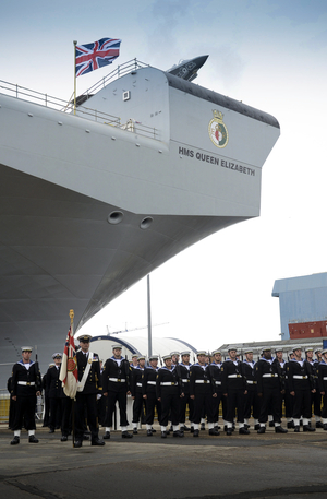 British Navy personnel stand to attention as Queen Elizabeth II smashes a bottle of whisky on the new aircraft carrier's bow.