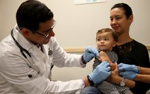 A two-year-old being vaccinated against measles.