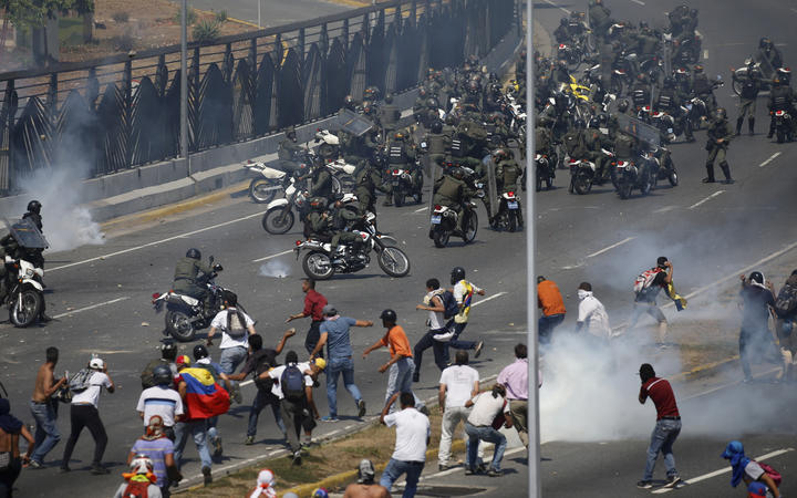 Opponents to Venezuela's President Nicolas Maduro confront loyalist Bolivarian National Guard troops firing tear gas at them, outside La Carlota military airbase in Caracas, Venezuela, Tuesday, April 30, 2019.