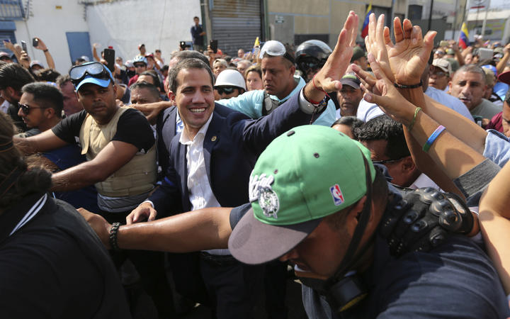 Venezuela's self-proclaimed president Juan Guaido greets supporters in Caracas, Venezuela, Tuesday, April 30, 2019.