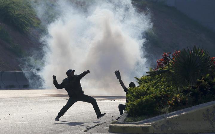 Opponents of Venezuela's President Nicolas Maduro throw stones at soldiers loyal to the president inside La Carlota airbase in Caracas, Venezuela, Tuesday, April 30, 2019.