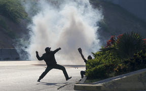 Opponents of Venezuela's President Nicolas Maduro throw stones at soldiers loyal to the president inside La Carlota airbase in Caracas, Venezuela, Tuesday, April 30, 2019.