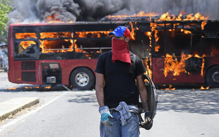 An opposition demonstrator walks near a bus in flames during clashes with soldiers loyal to Venezuelan President Nicolas Maduro near La Carlota military base in Caracas.