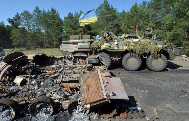 A Ukrainian  armoured personnel carrier drives past a burned armoured vehicle which was used by  pro-Russian militants near Sloviansk.