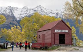 GLENORCHY, NEW ZEALAND - APRIL 2018: Tourists visiting the famed red hut at Glenorchy on the banks of Lake Wakatipu