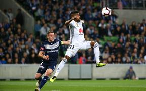 Roy Krishna of Wellington Phoenix controls the ball in front of Leigh Broxham of Melbourne Victory.