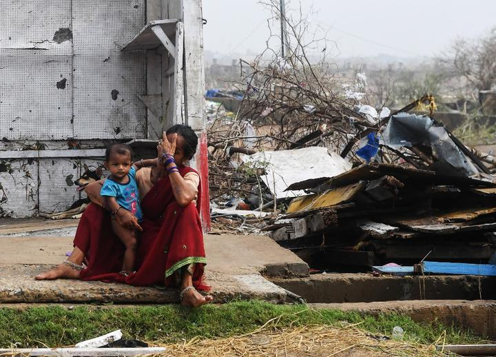 An Indian woman sits with her child next to storm-damaged buildings in Puri in the eastern Indian state of Odisha,