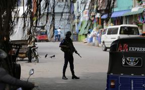 A Sri Lankan naval soldier stands guard at a road leading to a closed market on May Day in Colombo, Sri Lanka, Wednesday, May 1, 2019.
