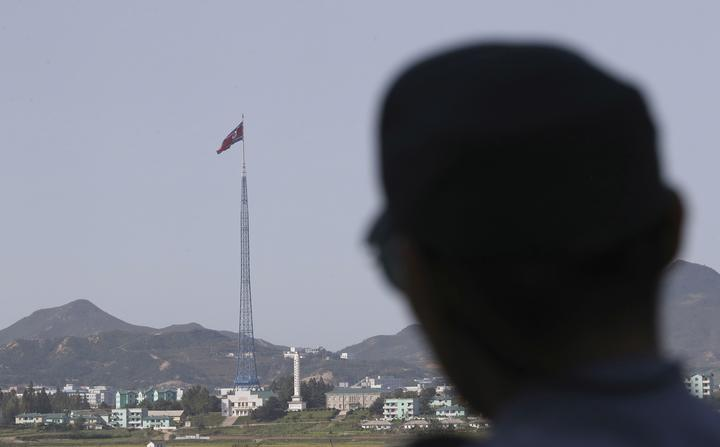 FILE - In this Sept. 28, 2017 file photo, A North Korean flag atop a 160-meter  tower in the North's Kijong-dong village as a South Korean soldier stands near the truce village of Panmunjom in the Demilitarized Zone which has separated the two Koreas since the Korean War, in Paju, South Korea.