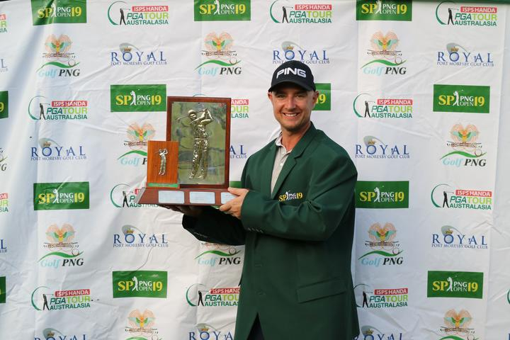 Peter Cooke lifts the PNG Open trophy.