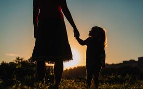 silhouette of mother and daughter holding hands in sunset nature