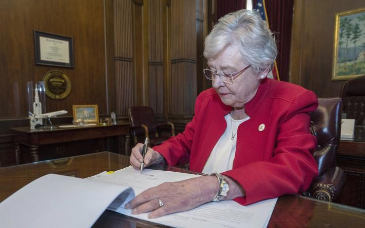 Alabama Governor Kay Ivey signing a bill that virtually outlaws abortion in the state.
