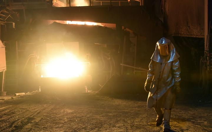 A steelworker in a protective suit checks the temperature of molten metal in furnace at a plant Pennsylvania.