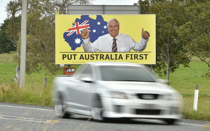 Photo taken on May 3, 2019 shows a ute driving past an election sign for mining magnate Clive Palmer's United Australia Party in Bowen in northern Queensland.