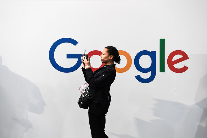 A woman takes a picture with two smartphones in front of the logo of the US multinational technology and Internet-related services company Google as he visits the Vivatech startups and innovation fair, in Paris on May 16, 2019.