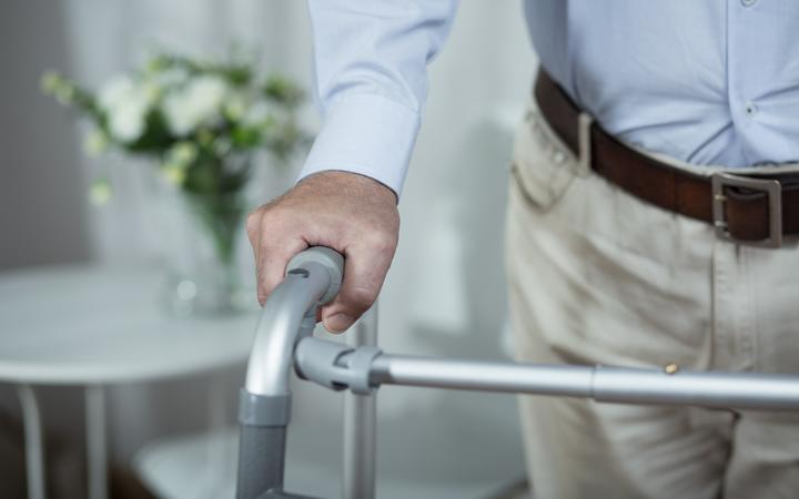 Elderly man. Walking frame. Retirement home.
