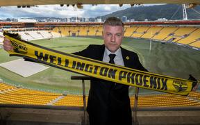New head coach of the Wellington Phoenix Ufuk Talay holds a Phoenix scarf at Westpac Stadium.