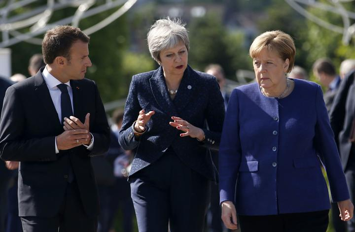 FILE - In this Thursday, May 17, 2018 file photo German Chancellor Angela Merkel, right, speaks with French President Emmanuel Macron, left, and British Prime Minister Theresa May